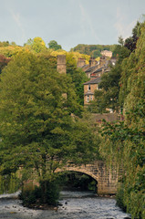 hebden bridge town in summer with packhorse bridge crossing the river calder and stone buildings in summer with bright sky and trees