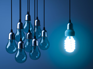 One hanging eco energy saving light bulb glowing and standing out from unlit incandescent bulbs on dark blue background , leadership and different creative idea concept. 3D rendering.