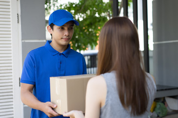 Handsome Young  man delivery person in blue uniform holding cardboard box send to customer,Delivery concept, Service concept.
