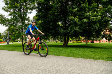 Young man biking in city park
