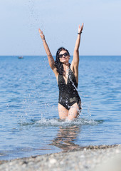 Woman in swimsuit and sunglasses splashing with arms raised