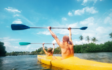 Father and son are sailing in the canoe in lagoon in sunny day