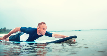 Man padding to line up on the surf board