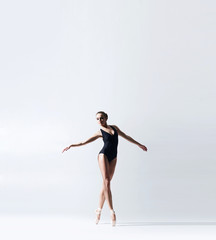 Ballerina in point shoes and bodysuit is dancing in studio. Young and graceful female ballet dancer.