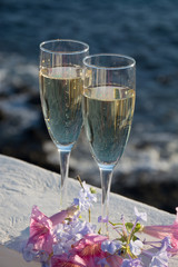 Two glasses with champagne or cava served outside on terrace, luxury resort with sea view, romantic vacation