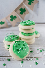 Saint Patrick's Day green cookies with sprinkles and shamrocks on light background