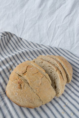 sliced homemade country bread loaf on striped table linen
