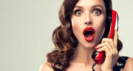 Beautiful woman in pin up style with vintage red phone.  Shocked pretty girl  . Presenting your...