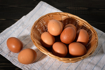 Fresh brown eggs on rustic, wooden, black, dark background