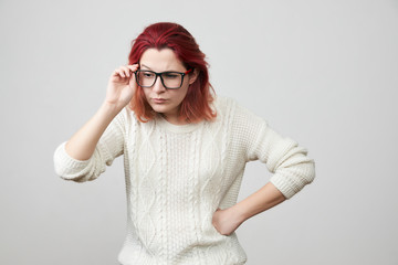 Portrait of young woman in white sweater with confused and gloomy expression, correcting glasses and puts one hand on her hip, isolated over gray background. The girl is indignant