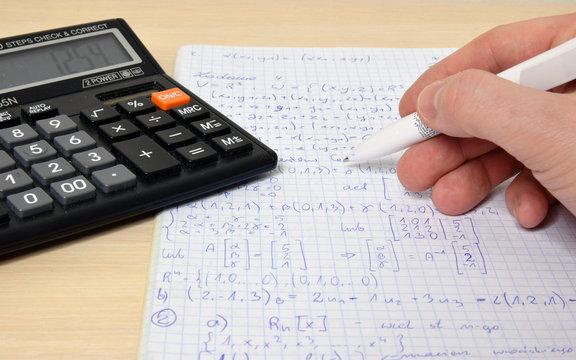 Solving math problems. Calculator, pen, hand.