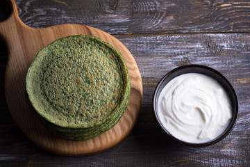 Wooden board with a stack of spinach pancakes and sour cream on the wooden table, rustic style, selective focus