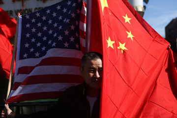 Man poses for a picture in front of the U.S. and Chinese flags at the Flushing Lunar New Year Parade in Queens, New York