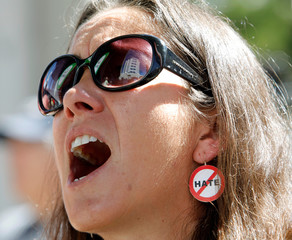 A protester wears an earring adorned with a message at a rally for gun control three days after the shooting at Marjory Stoneman Douglas High School, in Fort Lauderdale
