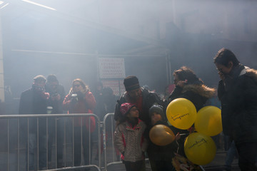 People watch a firecracker show at the Flushing Lunar New Year Parade in Queens, New York