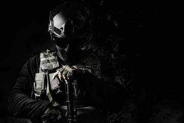 Black and white swat soldier posing with dissolving effect on black background.