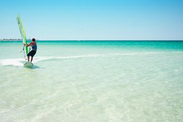 Windsurfer man exercising on a blue turquoise sea.