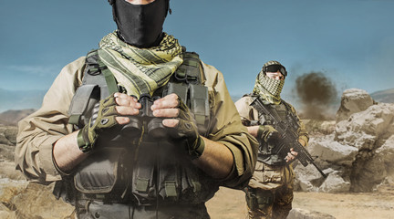 Photo of a fully equipped soldiers posing on a desert battlefield background.