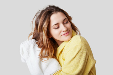 Pretty female with luxurious hair, wipes it with towel, takes bath, wears bathrobe, has soft healthy skin after taking shower, isolated over white background. People, wellness and hygiene concept