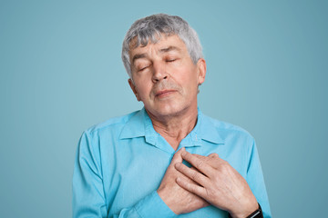 Portrait of handsome mature man with wrinkles keeps hands on heart, dressed in formal shirt, keeps eyes shut, expresses enjoyment towards something, isolated over blue background. Pleased grandfather