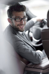 man in formalwear sitting in car