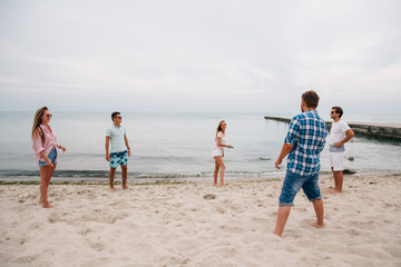 Group of young attractive friends playing frisbee on the beach, by the sea, spending weekend with pleasure.