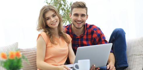 young couple .working on laptop sitting on sofa
