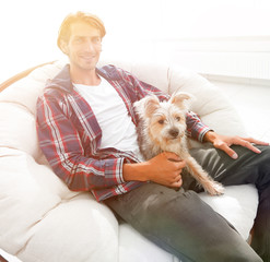 stylish guy sitting in a large comfortable armchair.