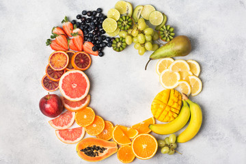 Wall Mural - Healthy eating, top view of healthy fruits in rainbow colours arranged in a circle frame, strawberries, mango, grapes, bananas, grapefruit on the off white table, copy space for text, selective focus