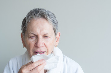 Head and shoulders view of older woman in white bathrobe in mid sneeze while holding tissue against neutral background (selective focus)
