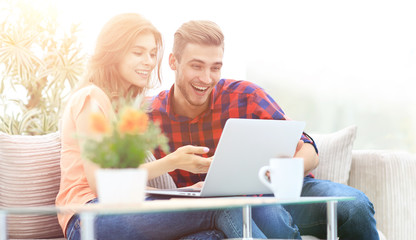 young couple looking at a laptop screen