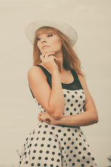 Beautiful retro style girl in polka dotted dress.
