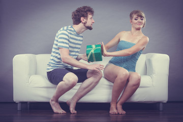 Young man giving offended woman gift box