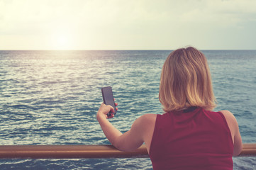 young women stand alone hold mobile phone for photography sea.