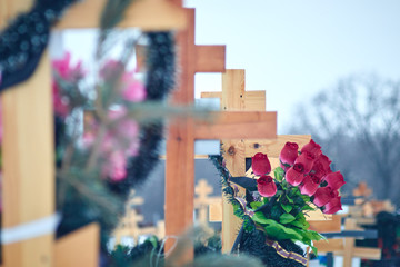 Orthodox cross in the cemetery. artificial flowers