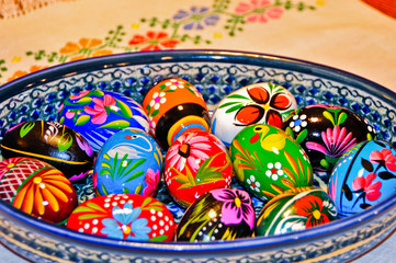 Colorful Hand Painted Wooden Easter Eggs in a Ceramic Bowl on a cloth with a needlepoint flower design.