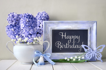 "Blue decorations and hyacinth flowers on white table, blackboard with text ""Happy Birthday"""