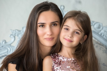 Portrait of mother and daughter in a beautiful interior room. Portrait, family values, childhood.