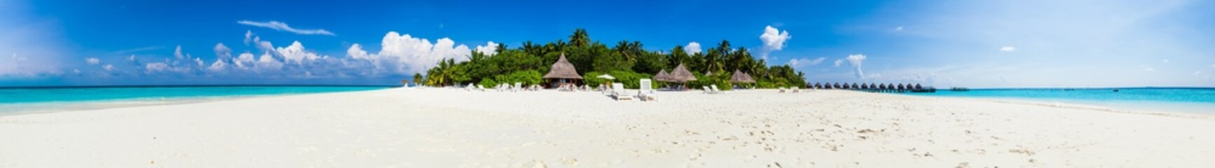 Panorama of a tropical island with white sand and palms.
