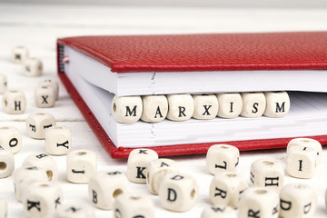 Word Marxism written in wooden blocks in red notebook on white wooden table.