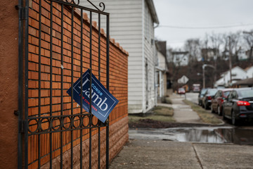 A sign showing support for Congressional candidate Conor Lamb hangs from, a gate in the town of Carnegie