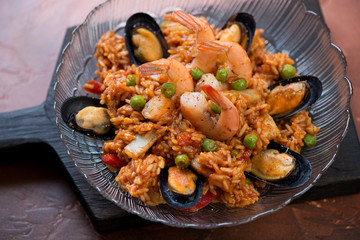Portion of paella with seafood on a black wooden serving board, selective focus, closeup