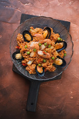 Plate of spanish seafood paella on a fire warm rusty metal background, view from above, vertical shot