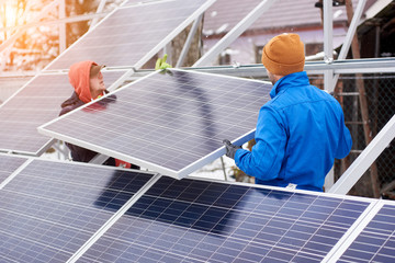 Engineers installing solar panels in winter. Outdoors. Workers are dressed in uniform and warmed with additional clothes
