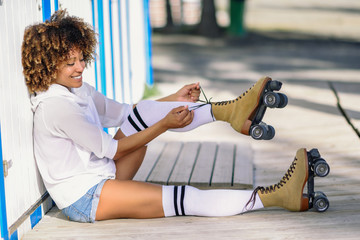 Young black woman sitting on wooden floor puts on skates.