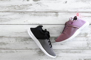 Sneakers (violet, black and white)  on wooden background with copy space. Active running (walking) footwear