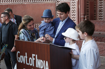 Canadian Prime Minister Justin Trudeau and his wife Sophie Gregoire help their son Hadrien to sign a visitor book as their daughter Ella-Grace and son Xavier look on during their visit to the Taj Mahal in Agra