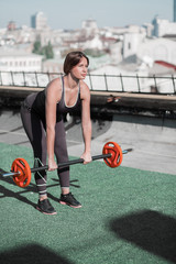 Sportive woman on the roof doing inclines with barbell. Woman taking care of her body, doing sport exercises.