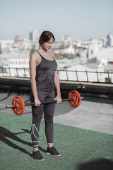 Young sportive woman holding barbell. Female doing sport exercises on the roof of the building,