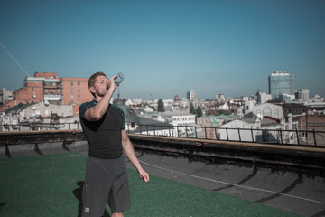 Sportive man drinking water after workout. Sprt on the roof of the building in the city, athletic male relaxing.